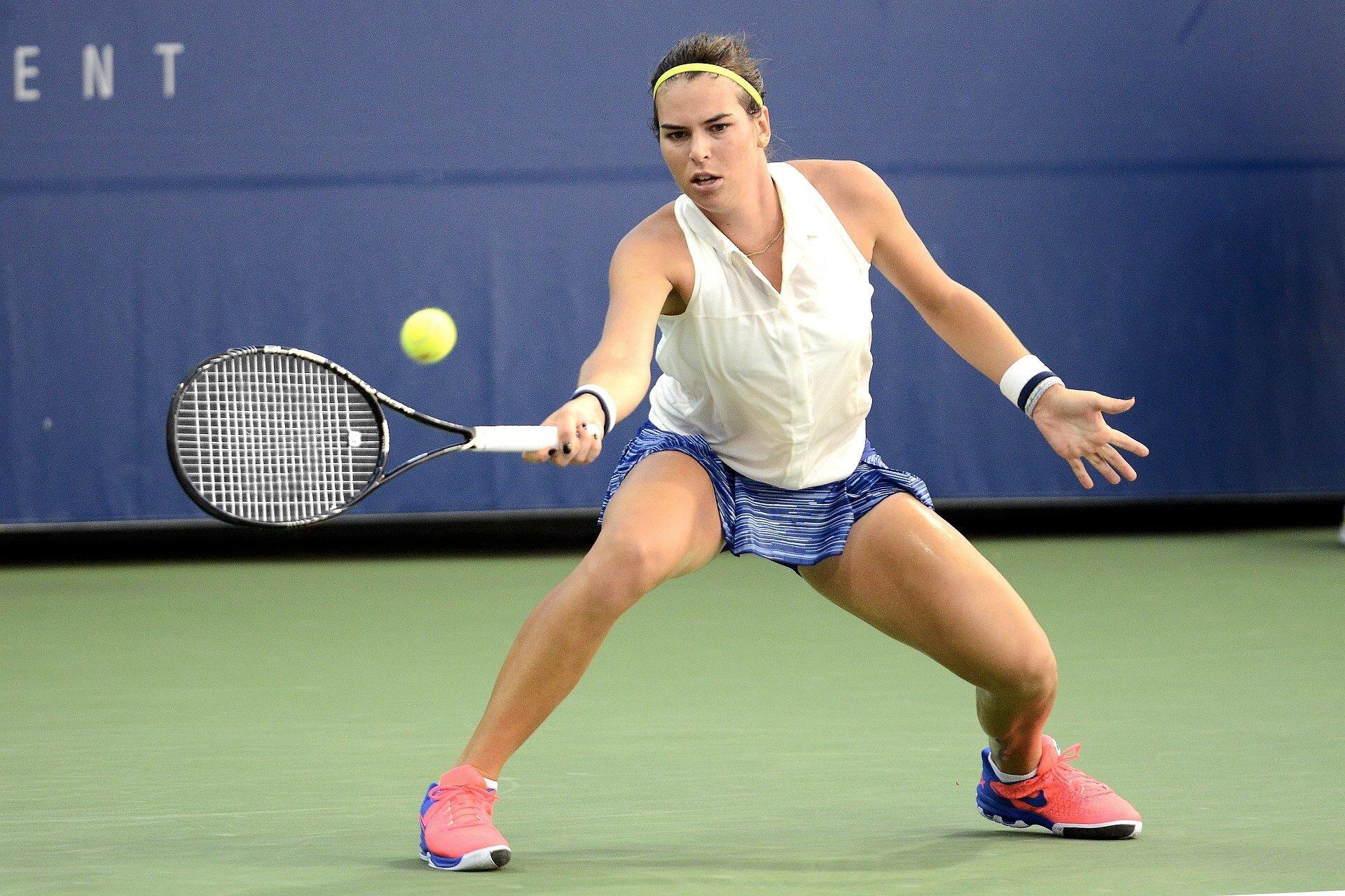 Zdjęcie przedstawia zawodniczkę podczas meczu tenisa ziemnego odbijającą piłkę zforehendu prawą ręką. Wzrok skupiony na piłce, mięśnie napięte, nogi wszerokim rozkroku iugięte wkolanach. Rakieta trzymana na wysokości bioder, piłka wpowietrzu tuż przed nią.