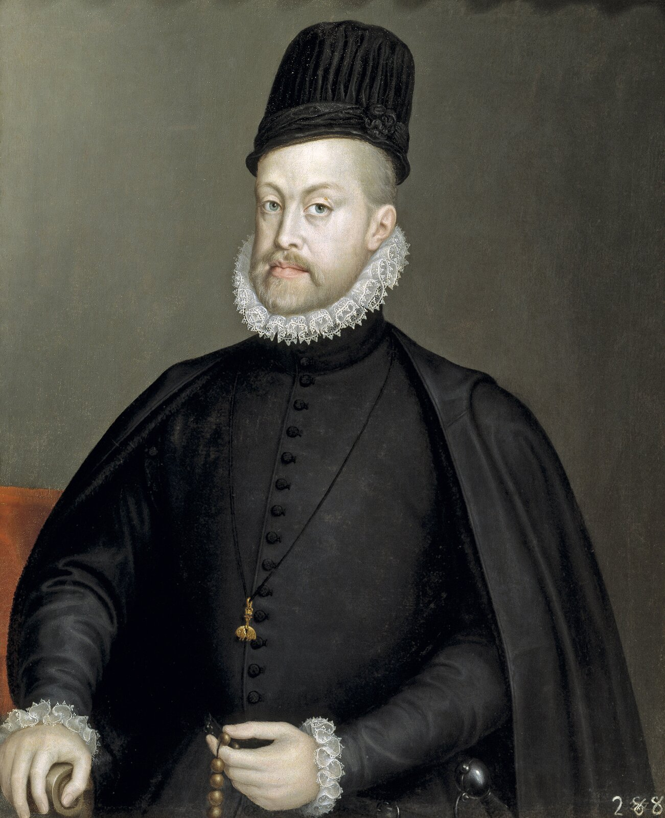 """Filip II FilipII wczarnym stroju, co było charakterystyczne wjego wyglądzie wlatach dojrzałych. Na szyi order Złotego Runa, wręku papieski tzw. """"złoty różaniec"""", wręczony mu uroczyście zokazji zwycięstwa nad flotą turecką pod Lepanto. Źródło: Sofonisba Anguissola, Filip II, 1565, olej na płótnie, Prado Museum, domena publiczna."""