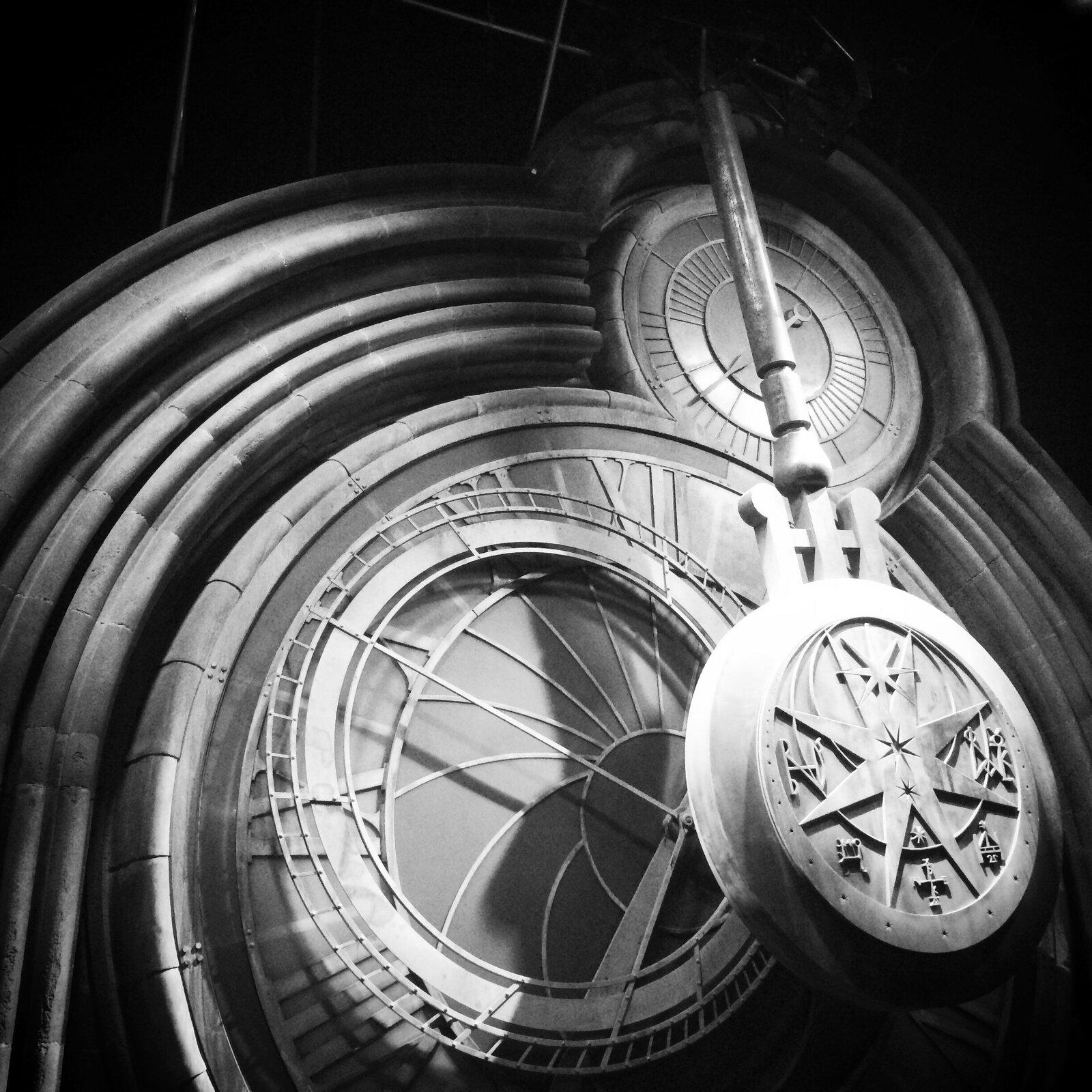 Czarnobiała fotografia okwadratowym układzie przedstawiająca wahadło zabytkowego zegara zwieży kościelnej zdobione symbolami astronomicznymi. Na tle odchylonego wahadła dwie tarcze zegarowe: większa wskazuje godziny ifazy księżyca oraz mniejsza minutowa umieszczona wgórnej części. Dookoła tarczy murowane wykończenie.