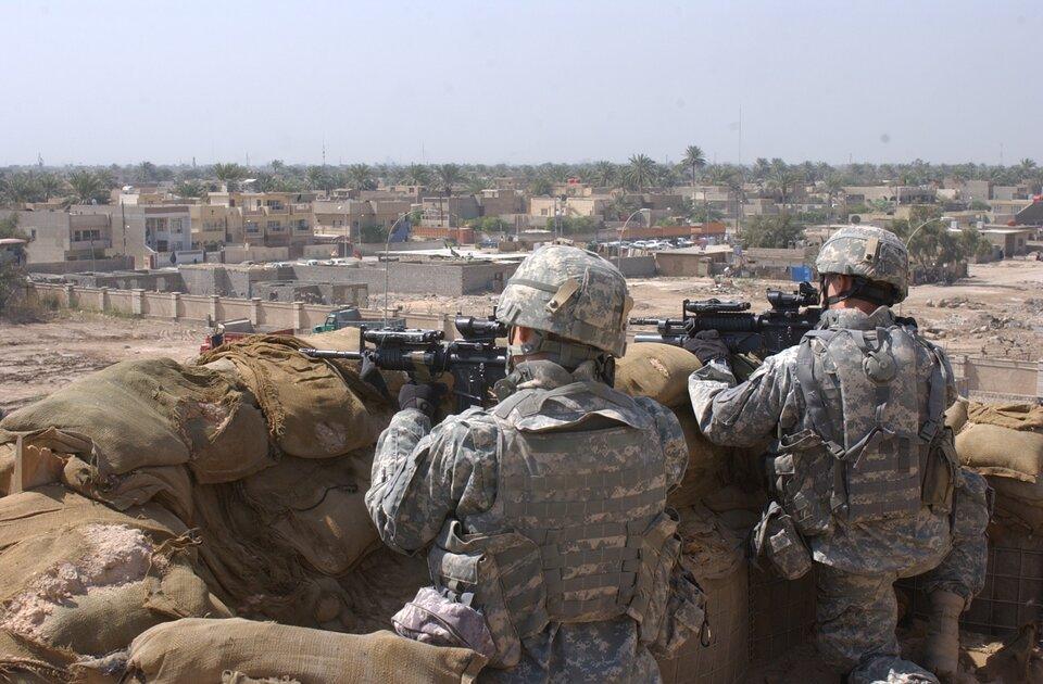 Na zdjęciu dwaj żołnierze mierzący zbroni palnej zza barykady zworków. Wtle teren zabudowany.