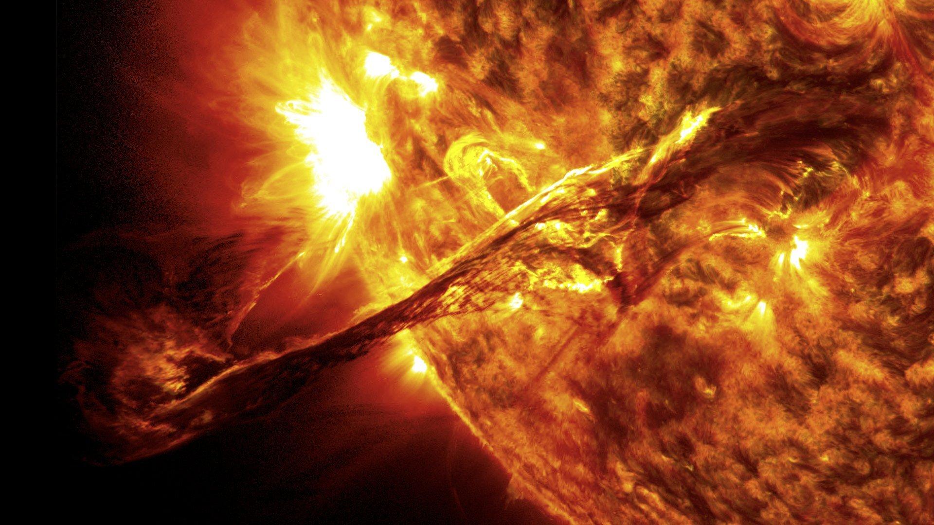 Zdjęcie przedstawia fragment Słońca podczas zjawiska koronalnego wyrzutu masy. Po prawej stronie kadru prezentowana jest tarcza słoneczna wpostaci wycinka czerwonożółtej kuli. Wgórnej części kadru na tej kuli znajduje się ogromna eksplozja wpostaci białej plamy, aponiżej jej podłużny obłok rozżarzonej materii wyrzucany jest wprzestrzeń kosmiczną. Wszystkiemu towarzyszą zakłócenia wyglądu powierzchni Słońca wtym obszarze, turbulencje ijaśniejsze plamy.
