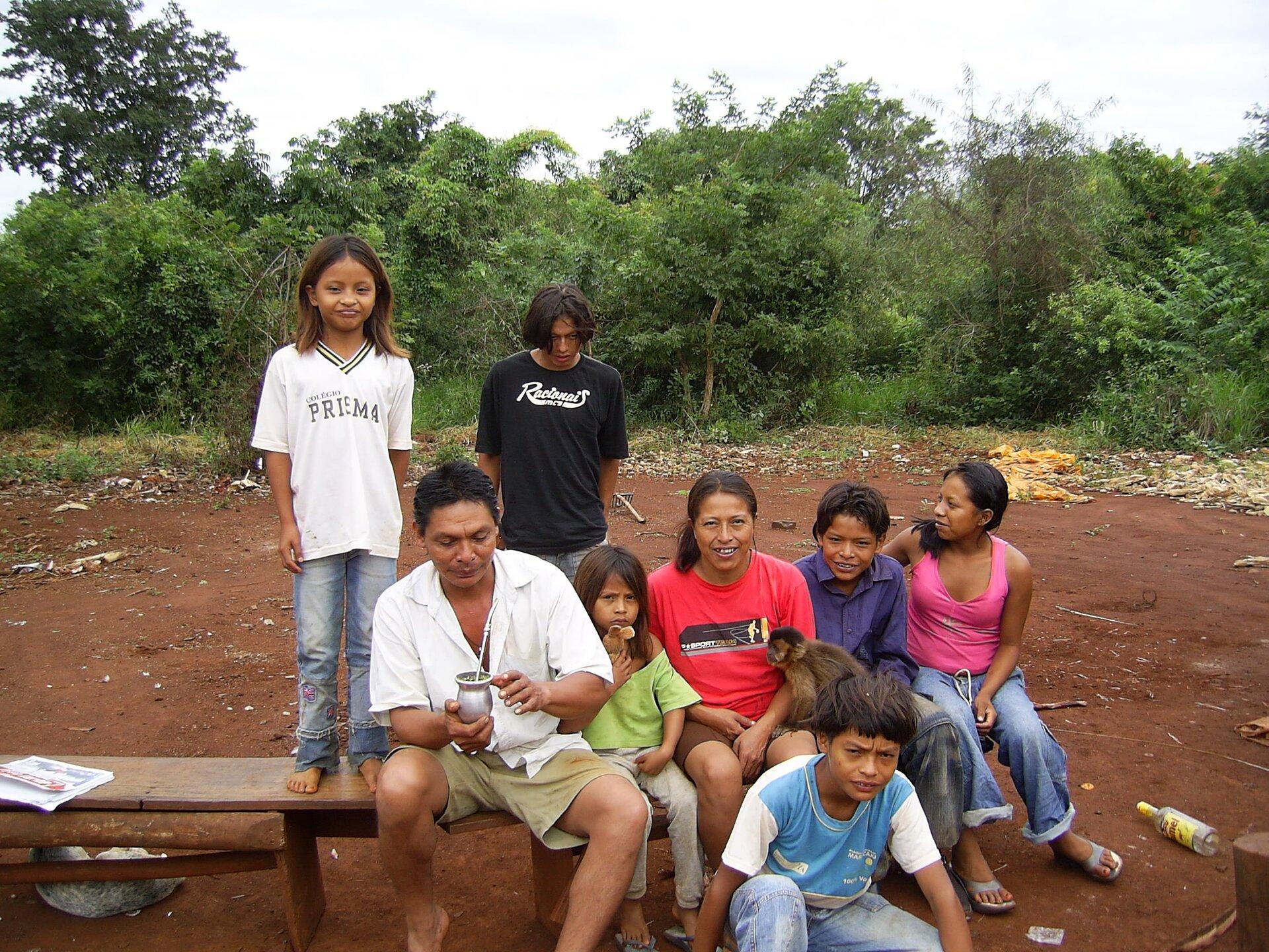 Na zdjęciu liczna rodzina pozuje do zdjęcia siedząc na ławce ustawionej na ceglastej ziemi. Na kolanach trzymają małpkę. Wtle zarośla.