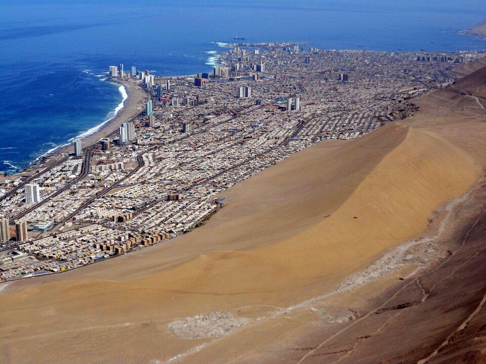 Na zdjęciu teren zabudowany nad morzem. Morze zlewej strony. Zprawej strony miasta olbrzymia wydma paraboliczna.