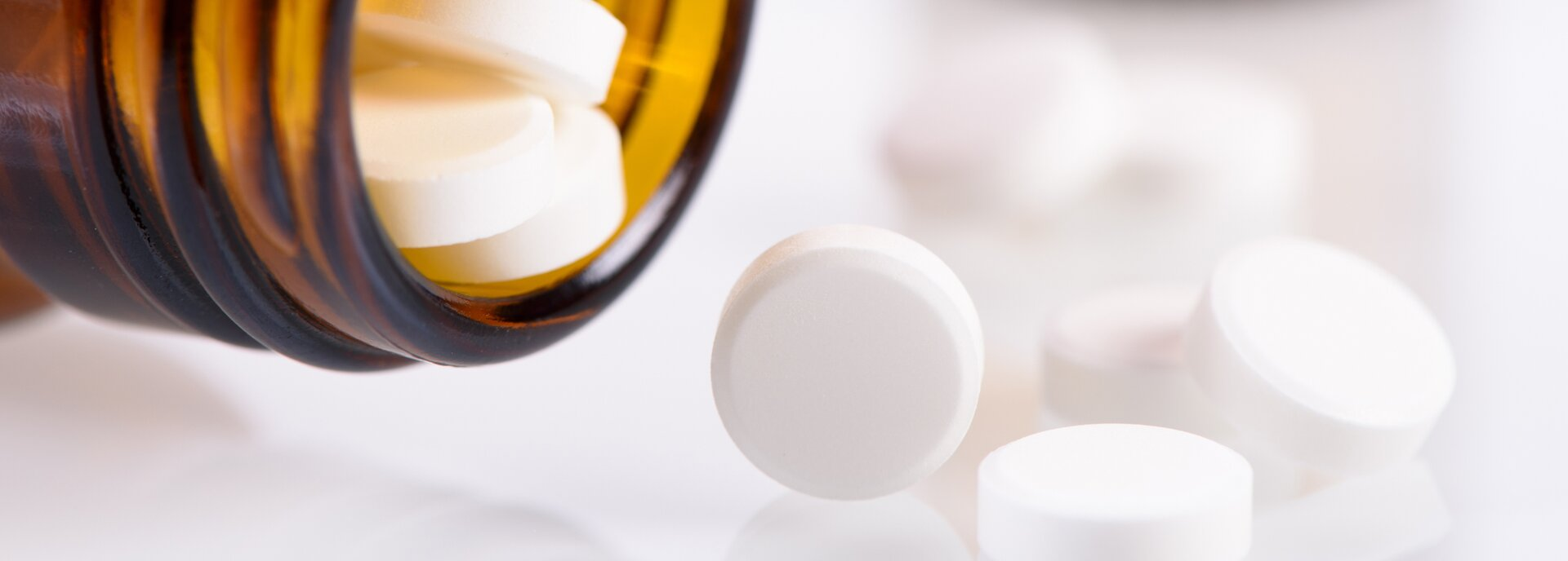 Kolorowe zdjęcie przedstawiające przechyloną na bok butelkę zbrązowego szkła, zktórej wysypują się białe okrągłe tabletki.