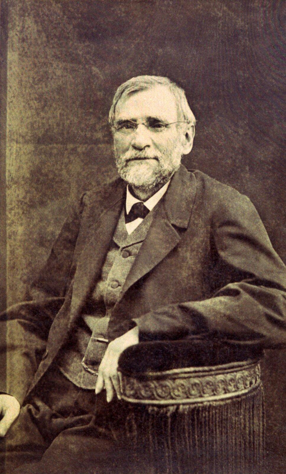 Na ilustracji portret Oskara Kolberga, autorstwa Walerego Rzewuskiego. Dzieło ukazuje starszego mężczyznę wpozycji siedzącej. Postać widoczna jest zprawego półprofilu. Mężczyzna ma siwe średniej długości włosy, siwą brodę iwąsy. Nosi okulary wdrucianych oprawkach. Mężczyzna ma na sobie koszulę, kamizelkę ifrak.