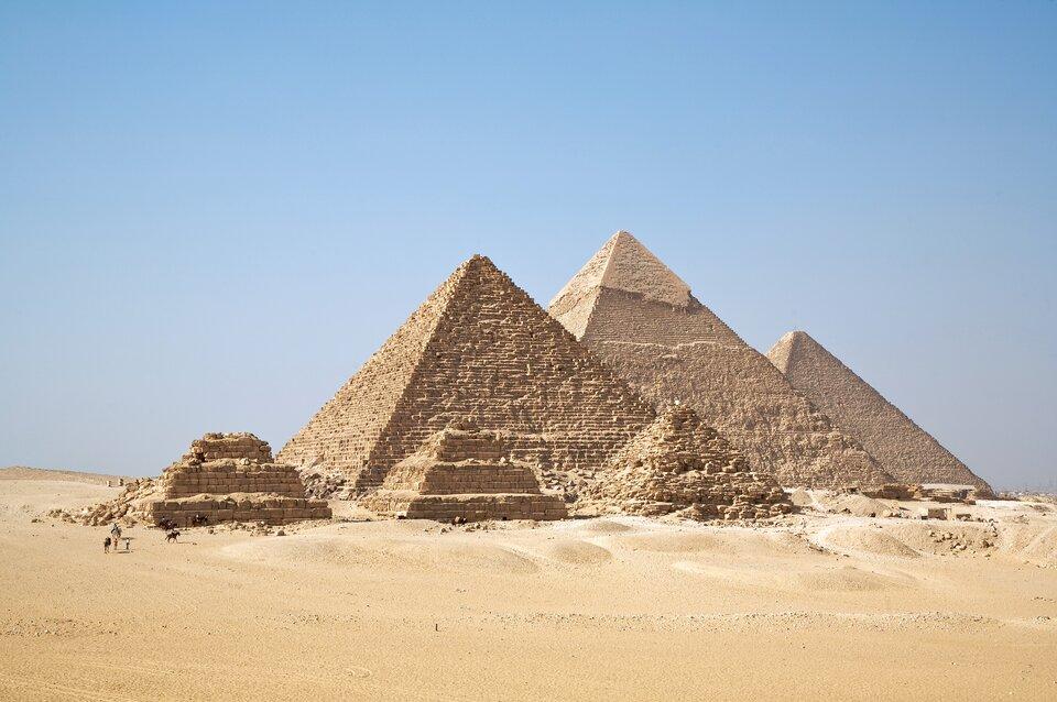 Na zdjęciu trzy duże piramidy, wkształcie ostrosłupa, na pierwszym planie trzy mniejsze piramidy. Stoją na piaszczystym terenie.