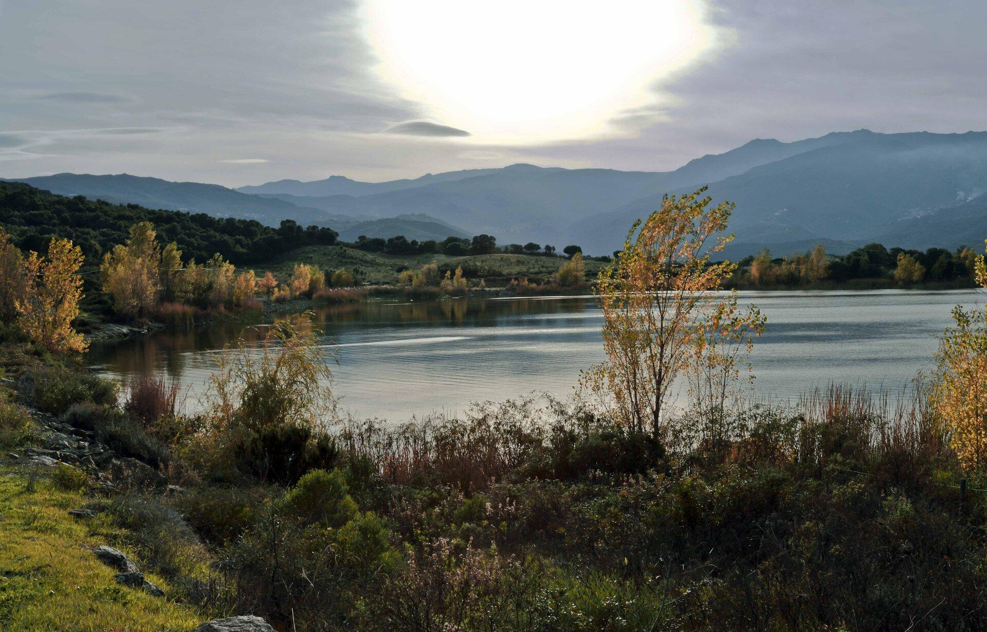 Fotografia prezentuje jezioro wokół, którego rosną różne rośliny zielne oraz drzewa. Wtle widoczne łańcuchy górskie.