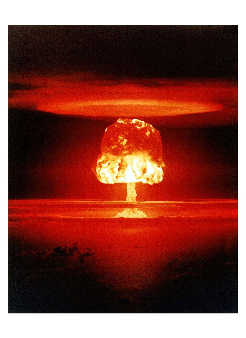 """Kolorowe zdjęcie 5: Castle Romeo. Zdjęcie przedstawia grzyb atomowy nad powierzchnią wody. Nad samą powierzchnią długa noga grzyba atomowego, powyżej kopuła grzyba. Grzyb to gęste kłęby chmur. Dolna część kopuły rozświetlona na pomarańczowo. Górna część kopuły jest czerwona. Nad grzybem ułożone są płasko chmury, które tworzą pierścień. Taki kształt określa się """"chmurą kalafiora""""."""
