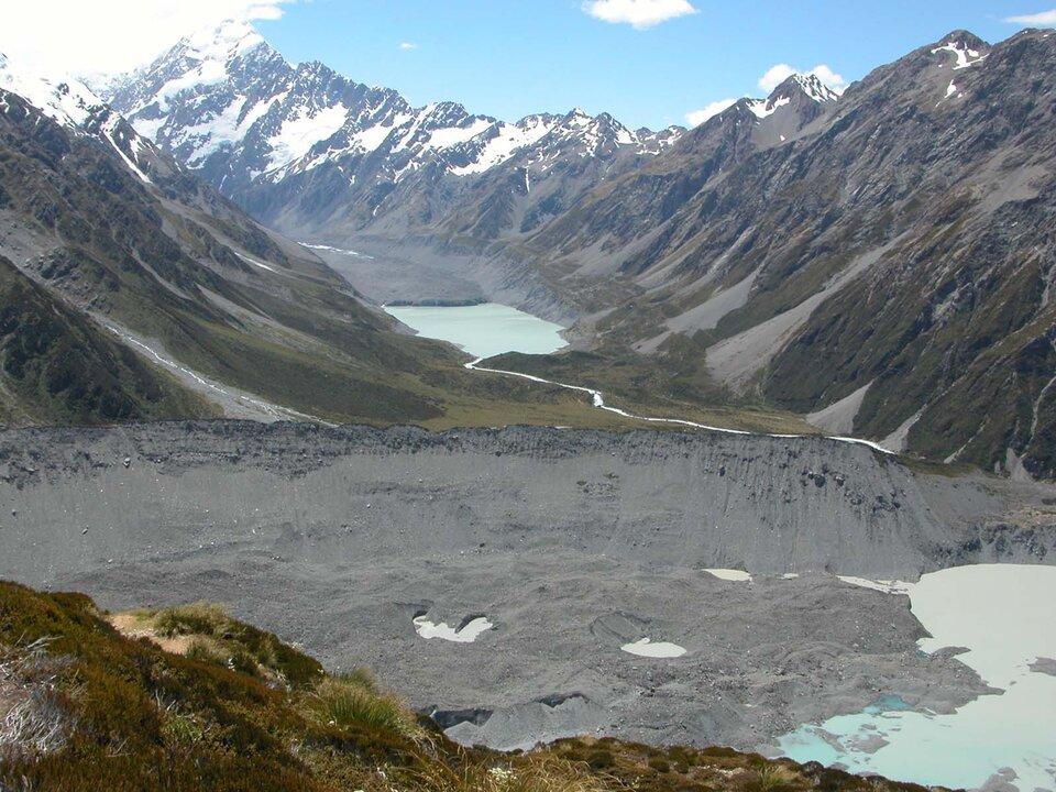 Na zdjęciu dolina U-kształtna. Wdnie doliny zbiornik wodny. Zbocza doliny są stokami pobliskich gór. Góry wysokie, skaliste. Na szczytach śnieg. Na pierwszym planie podłużny piaszczysty wał pozbawiony roślinności. Zprawej strony zbiornik wodny. Kilka zagłębień, które wypełnia woda.
