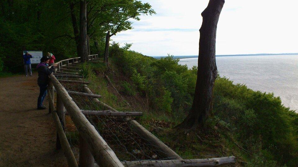 Na zdjęciu punkt widokowy ogrodzony drewnianą barierką, tablica informacyjna, wdole morze.