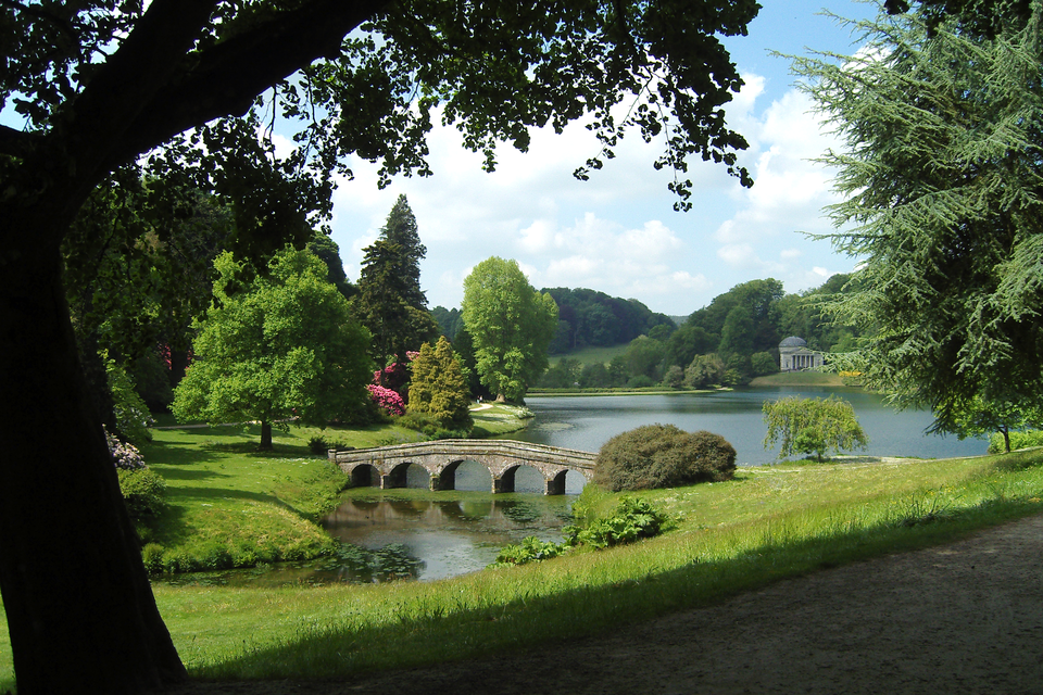 Fotografia prezentuje park położony nad wodą zróżnymi drzewami oraz krzewami.