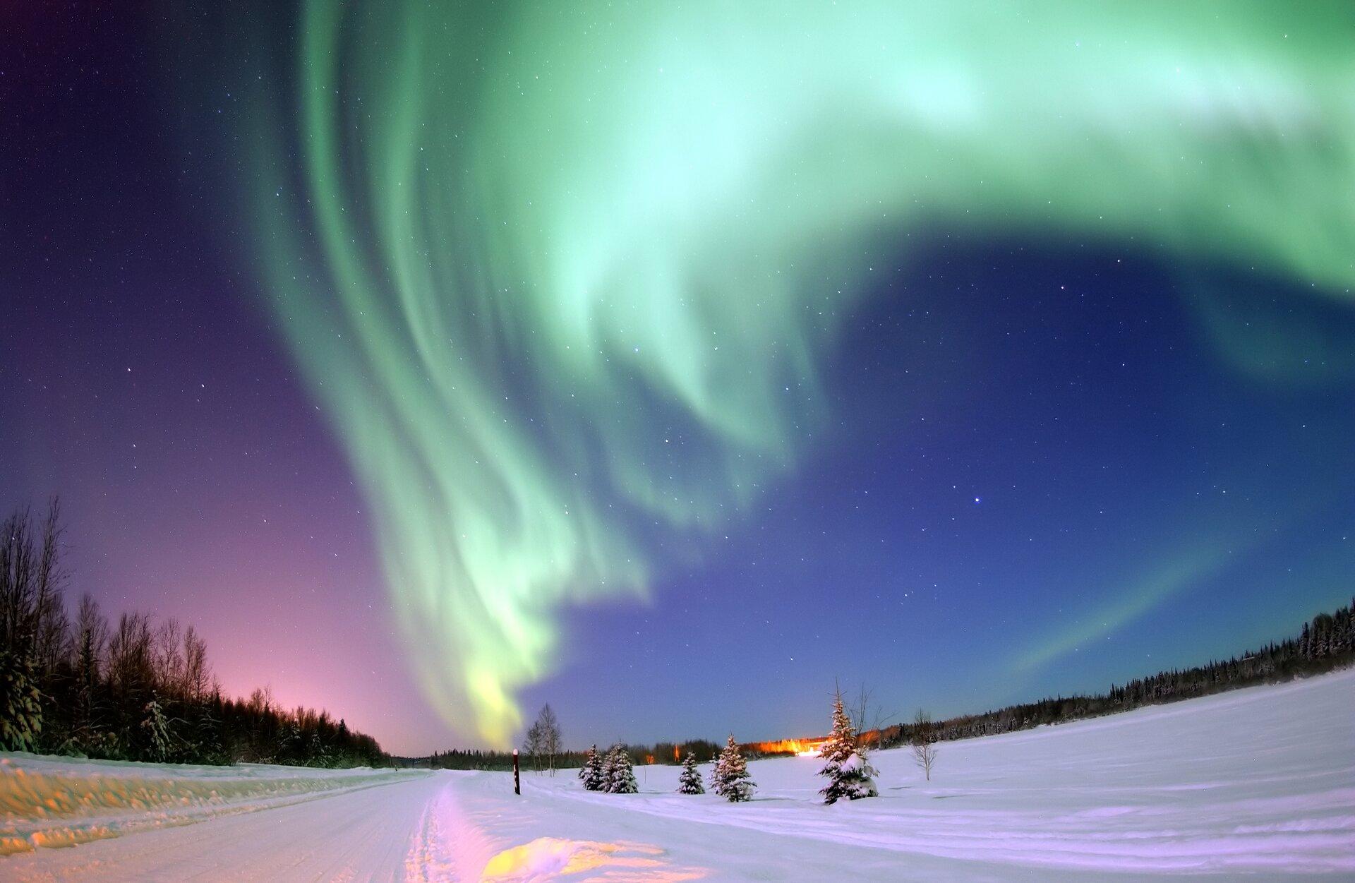 Zdjęcie przedstawia zorzę polarną nad pokrytą śniegiem drogą, okolicznymi lasami ipolami. Ilustracja stanu plazmy.