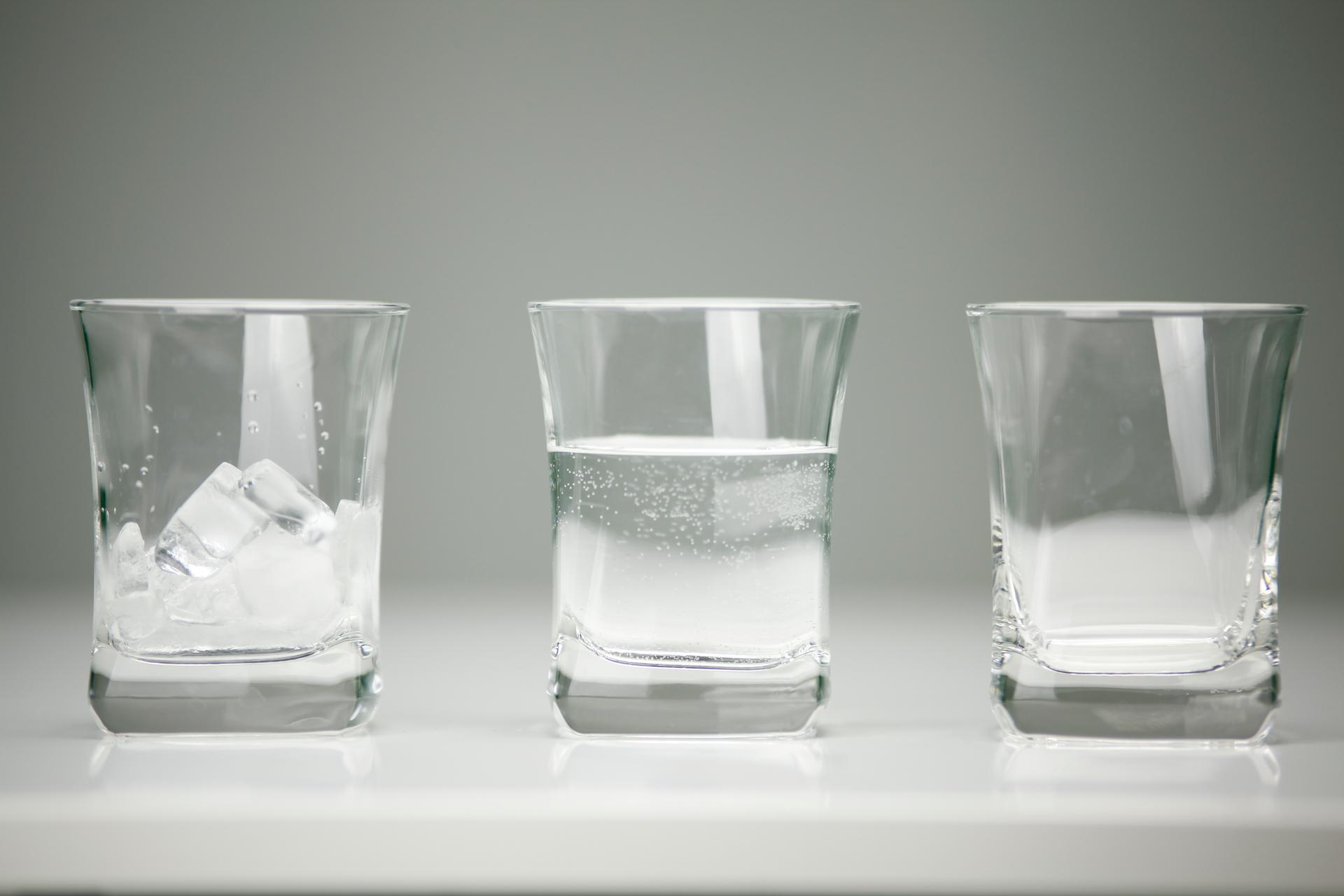 Fotografia trzech szklanek. Wpierwszej kilka kostek lodu. Wdrugiej woda. Trzecia szklanka pusta.