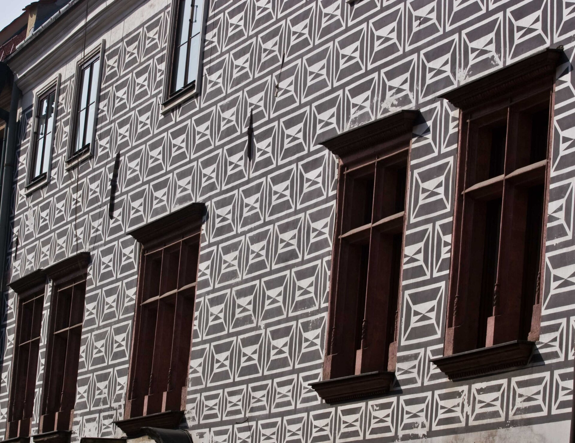 Ilustracja przedstawia sgraffito wykonane na fasadzie budynku. Dekoracja imituje renesansowe okładziny kamienne wkolorze jasnoszarym na ciemnoszarym tle.