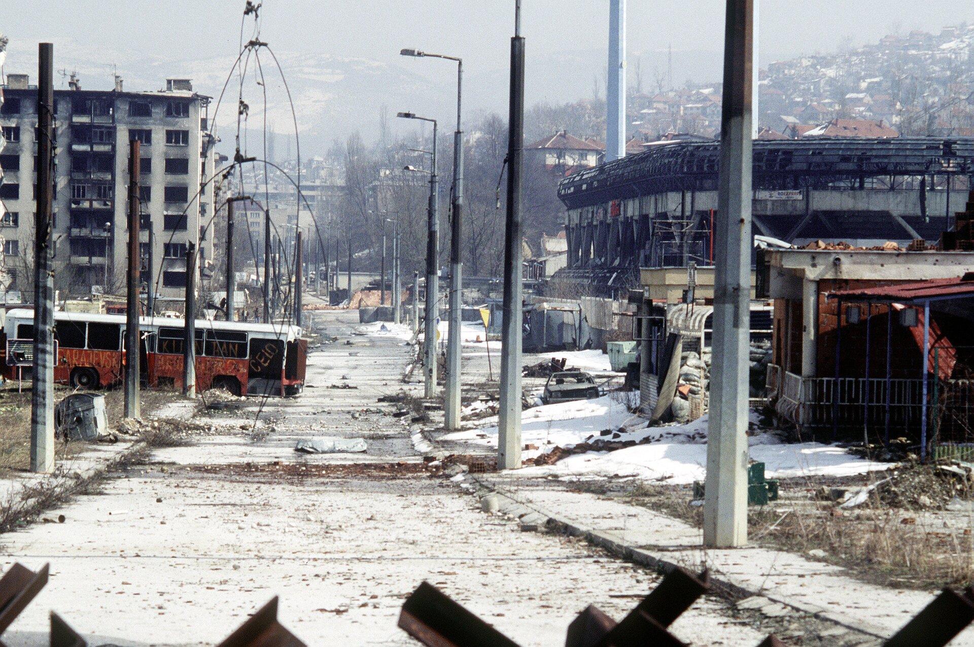 Zdjęcie przedstawia Sarajewo po wojnie wlatach 1992 – 1996. Środek zdjęcie zajmuje asfaltowa ulica biegnąca wzdłuż centrum miasta. Po obu stronach wysokie betonowe latarnie. Wgłębi zdjęcia zniszczony spalony autobus. Autobus stoi wpoprzek . Po obu stronach ulicy zniszczone zabudowania. Ulica, chodniki, pobocza ibudynki są pokryte cienką warstwą śniegu. Wgłębi zdjęcia, za miastem, budynki na zboczu wzgórza. Wzgórze znajduje się po prawej stronie miasta. Dachy budynków pokryte białą warstwą śniegu.