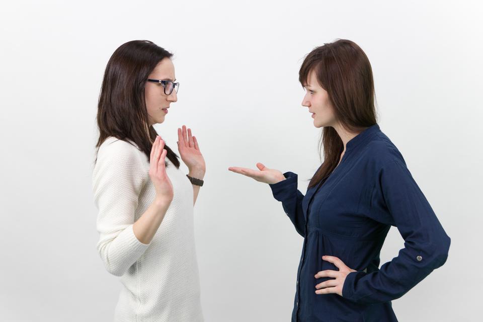 Fotografia przedstawia dwie dziewczyny stojące naprzeciwko siebie, zwrócone przodem do siebie. Dziewczyny dyskutują lub kłócą się, gestykulując.