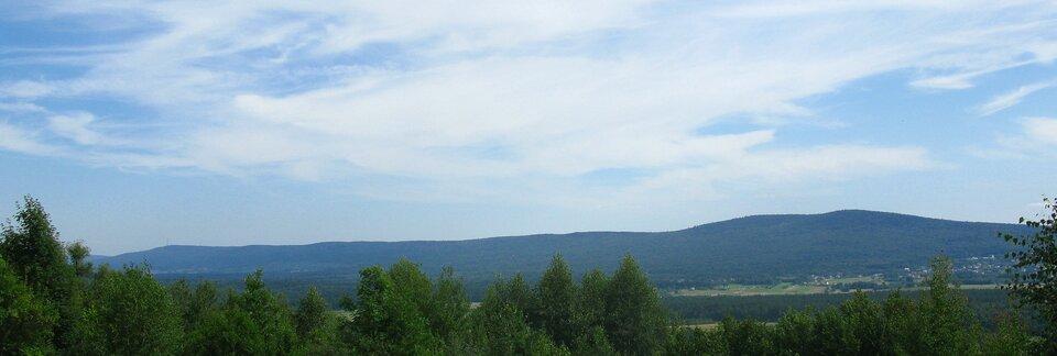 Na zdjęciu na pierwszym planie płaski teren, dalej wtle niskie łegodne góry porośnięte lasami.