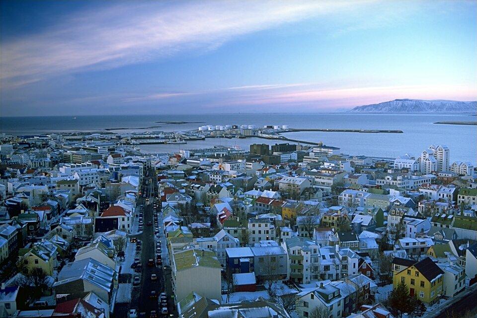 Na zdjęciu panorama miasta zimą, zwarta niska zabudowa. Domy mają bardzo kolorowe elewacje irównie kolorowe dachy. Środkiem biegnie ulica. Miasto położone nad zatoką, wtle górzysty brzeg.