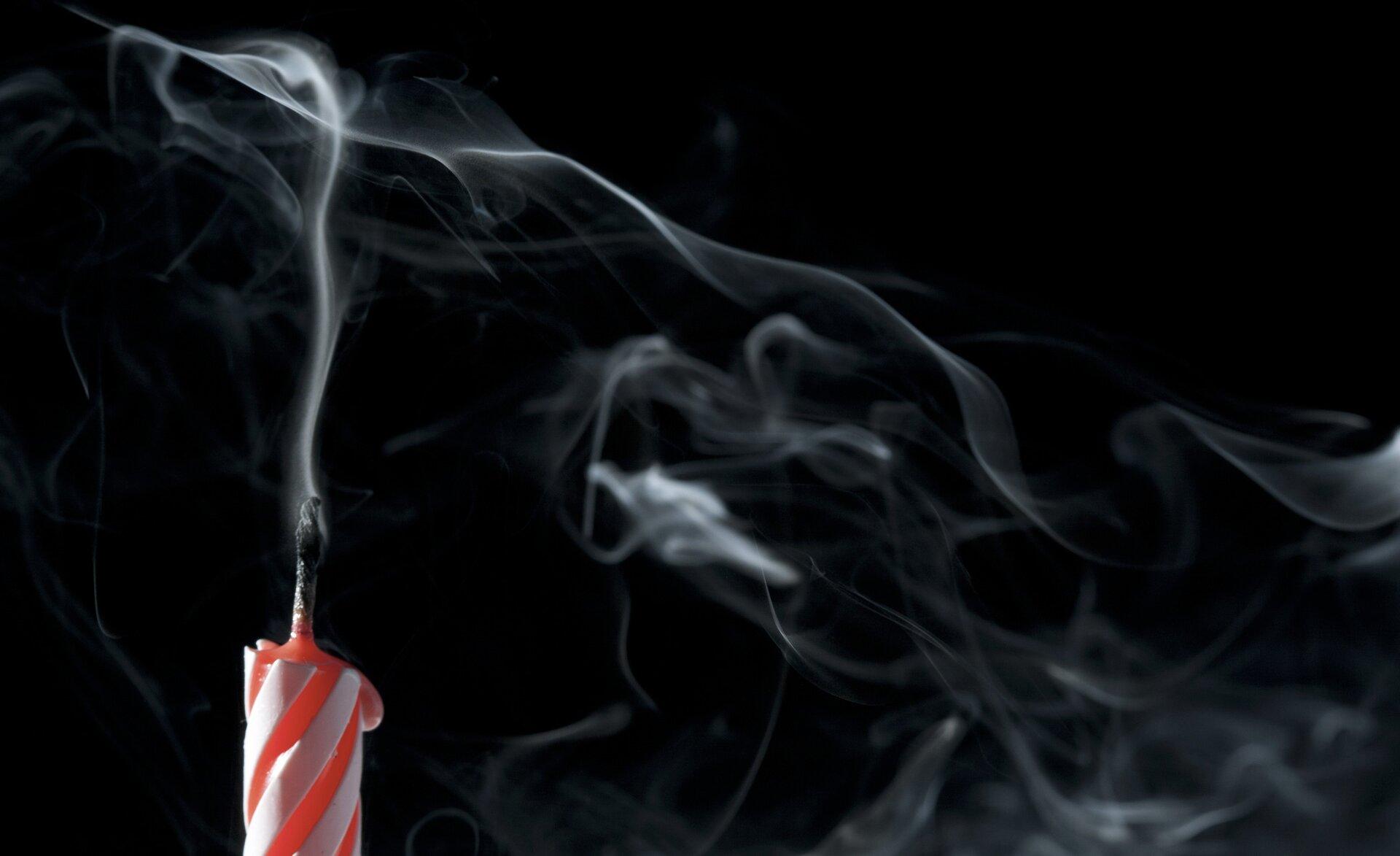 Zdjęcie przedstawia zgaszoną urodzinową, czerwono białą pasiastą świeczkę na czarnym tle. Świeczka znajduje się wlewym dolnym rogu kadru, oświetlona jest zlewej strony. Knot niedawno zgaszony, dymi się jeszcze. Resztę kadru wypełnia czarne tło oraz zakręcone smugi szarego dymu mającego swój początek wknocie.