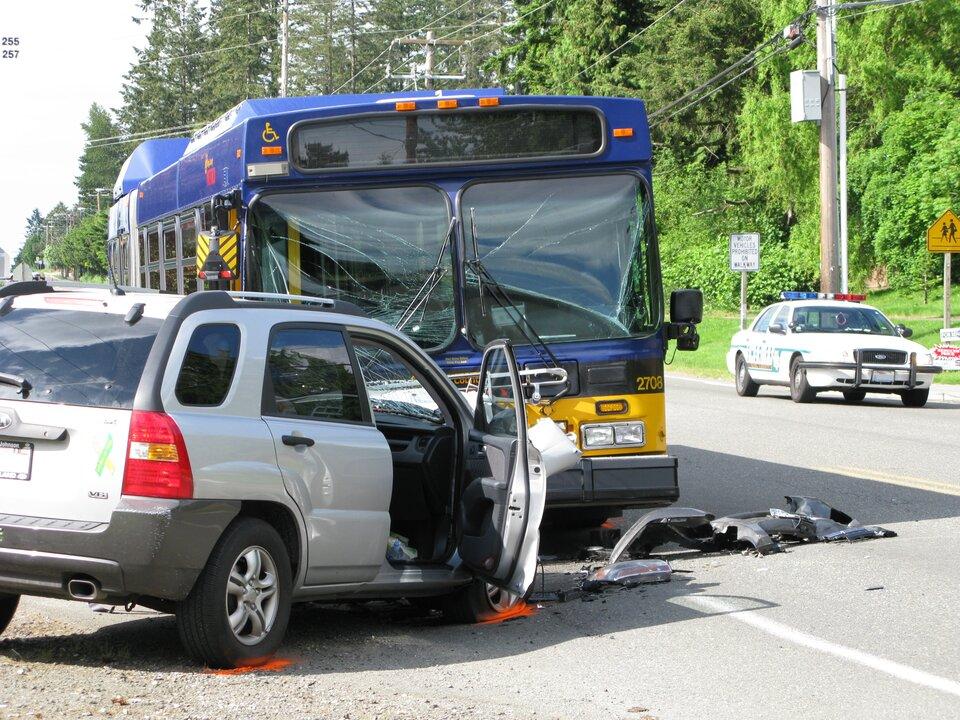 Zdjęcie przedstawia wypadek drogowy zudziałem autobusu. Słoneczny dzień. Autobus isamochód osobowy znajdują się na asfaltowej dwupasmowej jezdni. Niebiesko żółty autobus ustawiony przodem do obserwatora zdjęcia. Biały samochód osobowy bokiem do obserwatora zdjęcia. Przednie szyby autobusu są pęknięte poprzecznie, ale nadal na miejscu. Samochód osobowy, który zderzył się zautobusem czołowo ma całkowicie zniszczony przód. Na asfalcie kawałki czarnego zderzaka samochodu. Drzwi pasażera otwarte. Widoczne wkadrze koła samochodów mają oznaczone pomarańczową farbą wspreju miejsca, wktórych stykają się zasfaltem. Wtle, na prawo, samochód policyjny. Na dachu samochodu policyjnego niebieskie iczerwone prostokątne światła.