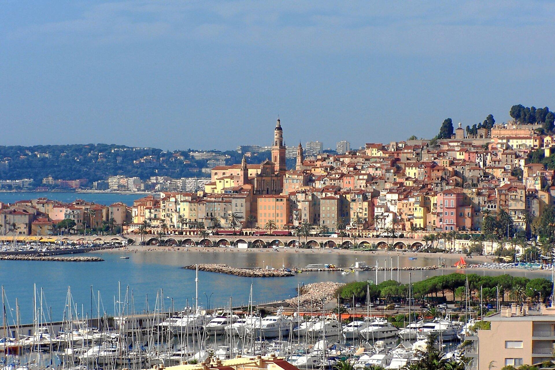 Na zdjęciu gęste zabudowania nad brzegiem morza. Teren górzysty, budynki stoją piętrowo. Zacumowane łodzie.