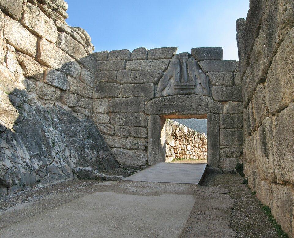 Na zdjęciu kamienna brama wmurze. Nad otworem wejściowym trójkątna płyta zpłaskorzeźbą zlwami.