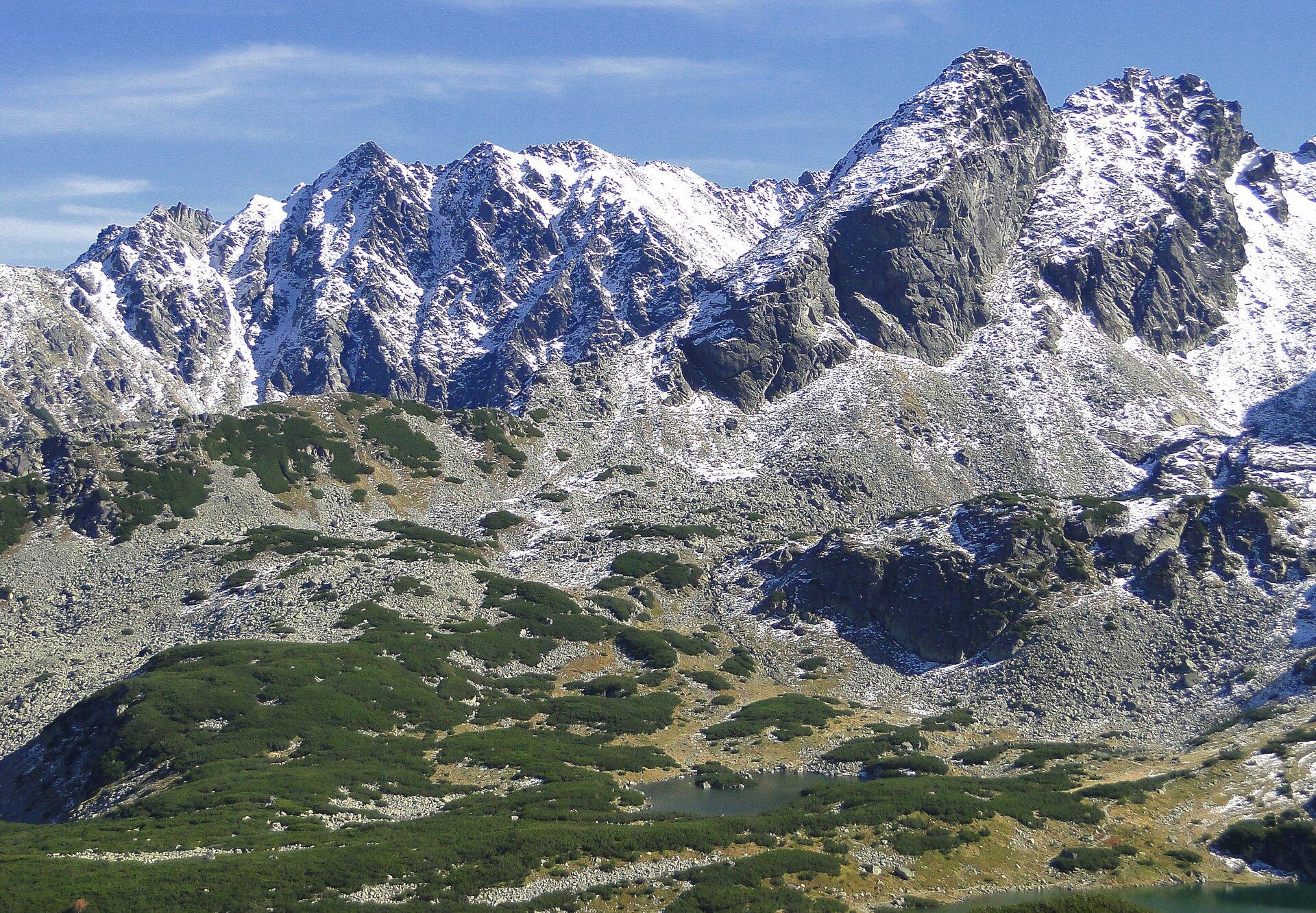 Trzecia fotografia, to góry wysokie Tatry, widoczne wysokie nagie szczyty górskie.