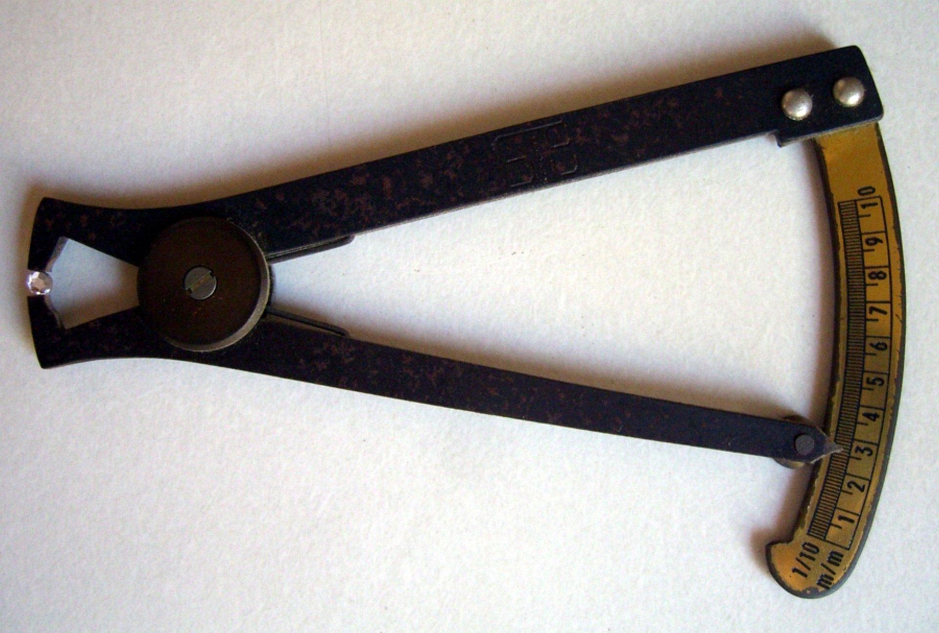 Jubilerski przyrząd pomiarowy suwmiarkowy na białym tle, przypominający kleszcze zpodziałką na rączce mierzącą szerokość rozwarcia szczęk. Wszczękach przyrządu znajduje się mały bezbarwny kamień, ajego wymiary odczytywane na skali to 2,6 mm.
