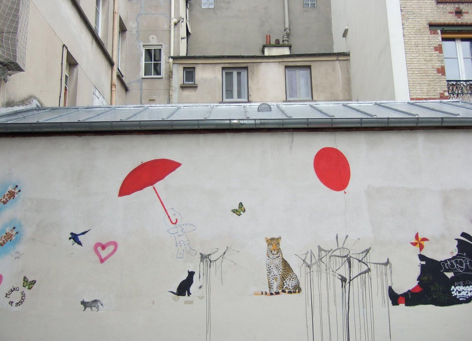 Ilustracja przestawia mural Mosko et Associes. Ukazuje namalowane na ścianie, swobodnie rozmieszczone: czerwone parasol ibalon, czarnego kota, tygrysa, ptaki, motyla isiedzącego mężczyznę. Za murem znajdują sie budynki.