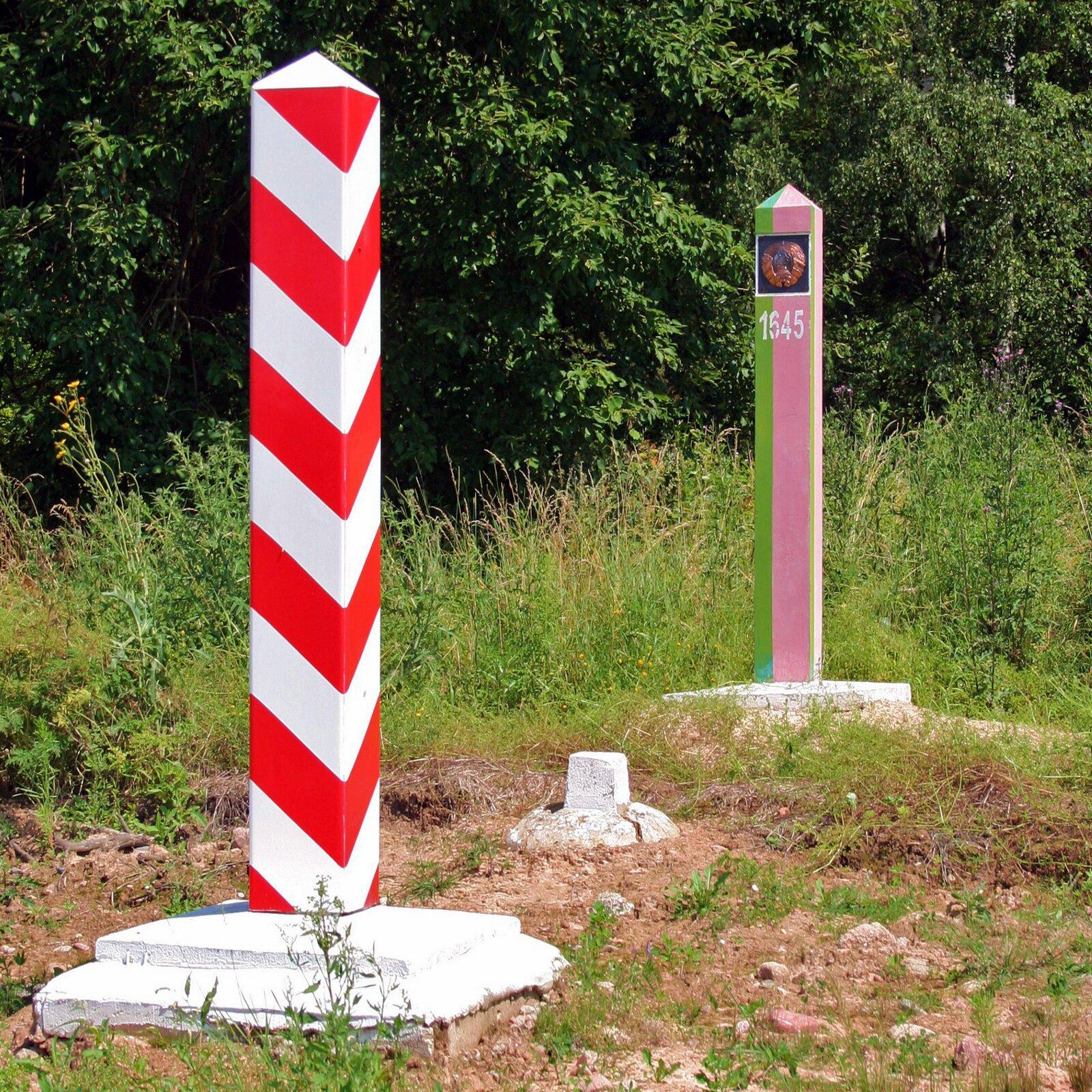 Fotografia prezentuje dwa znaki graniczne. Na pierwszym planie słupek pomalowany wpoziome biało-czerwone pasy, na drugim planie słupek pomalowany wpionowe fioletowo-zielone pasy znumerem iemblematem na szczycie.