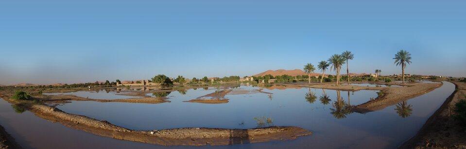 Na zdjęciu oaza. Zbiornik wodny, dookoła palmy. Wtle zabudowania ipasmo gór.