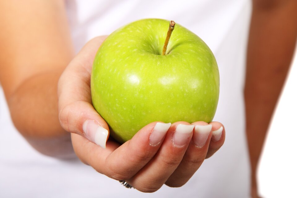 Fotografia przedstawia zielone jabłko wkobiecej dłoni