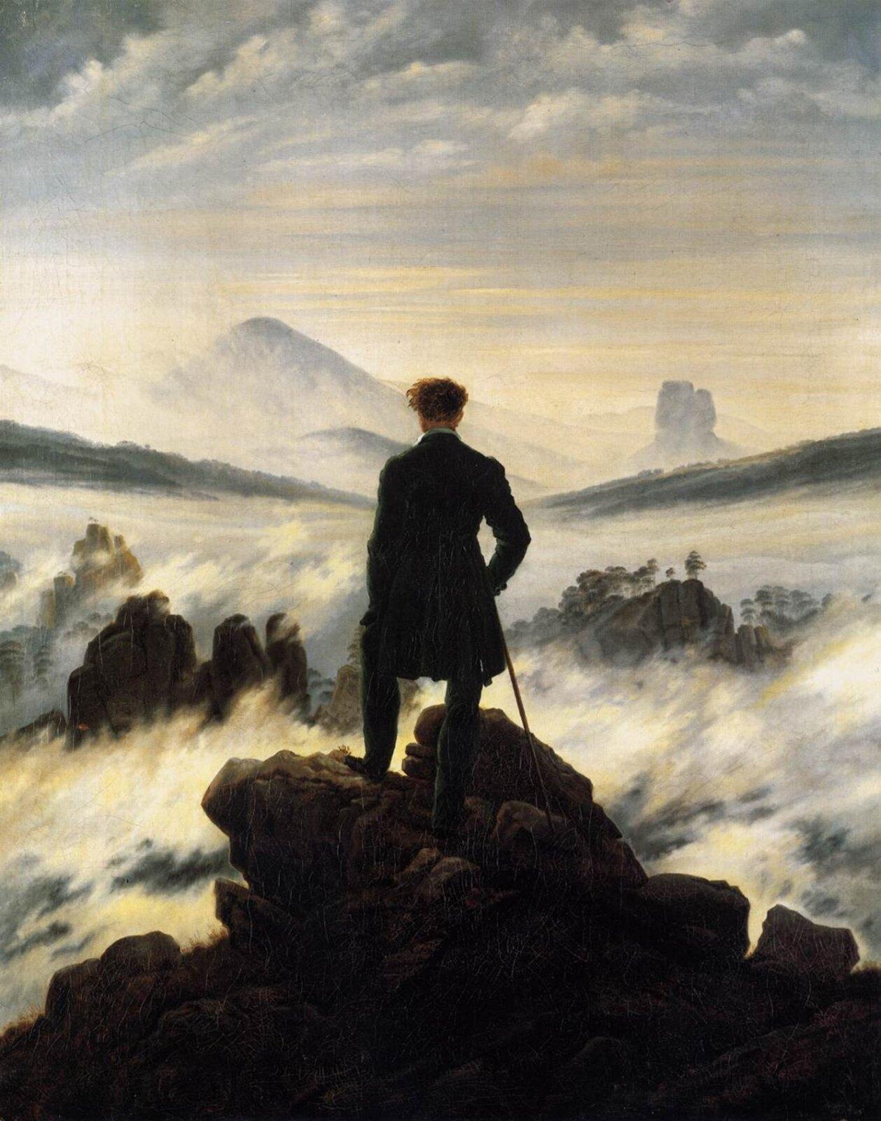 """Ilustracja przedstawia obraz Caspara Davida Friedricha pt. """"Wędrowiec nad morzem mgły"""". Na obrazie widzimy samotnego, romantycznego wędrowca. Mężczyzna stoi tyłem, na skalistej górze. Wprawej dłoni trzyma drewnianą laskę. Ubrany jest we frak. Krajobraz jest piękny przedstawia zamglone góry."""
