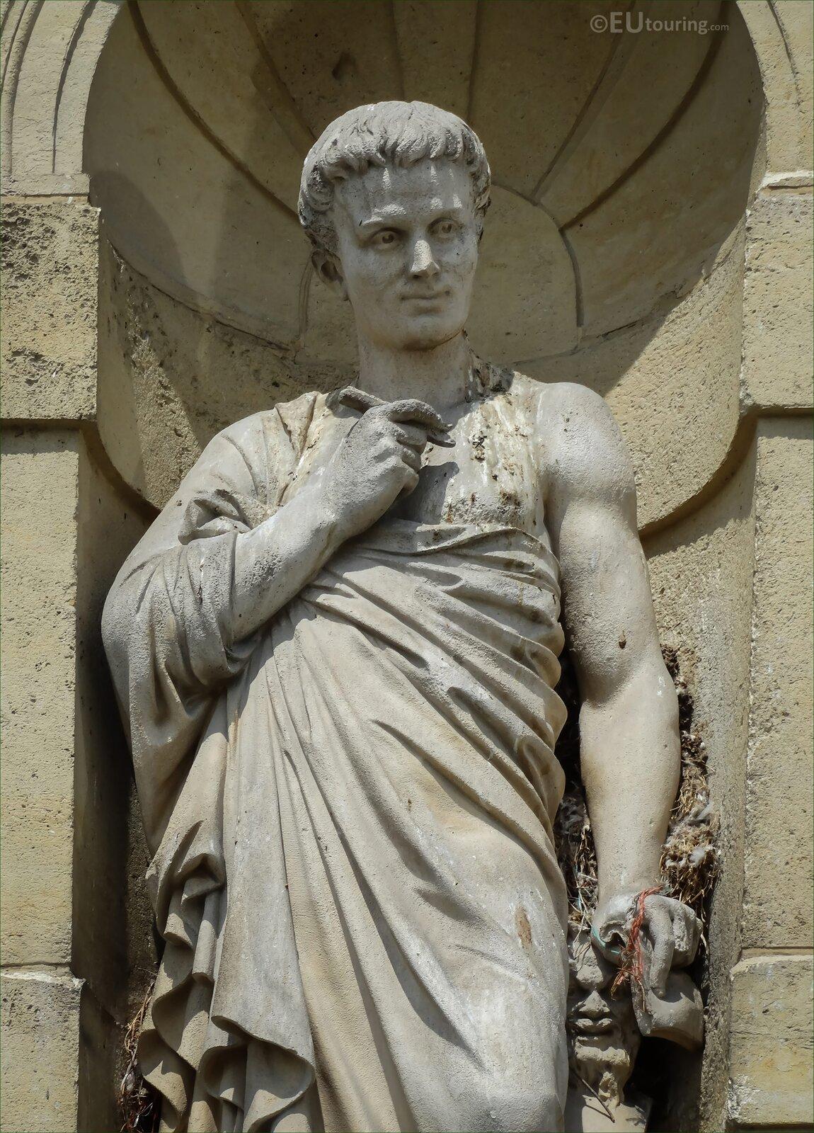 """Rzeźba nieznanego autora pod tytułem """"Horacy"""", przedstawia postać młodego mężczyzny ośredniej długości włosach. Horacy spogląda wprawo, ubrany jest wdługą szatę, wjednej dłoni trzyma ołówek, adrugiej zwitek papierów. Rzeźba została wykonana zjasnego kamienia, na figurze widoczne są liczne zabrudzenia, oraz ubytki. Figura Horacego stoi we wnęce izostała sfotografowana za dnia."""