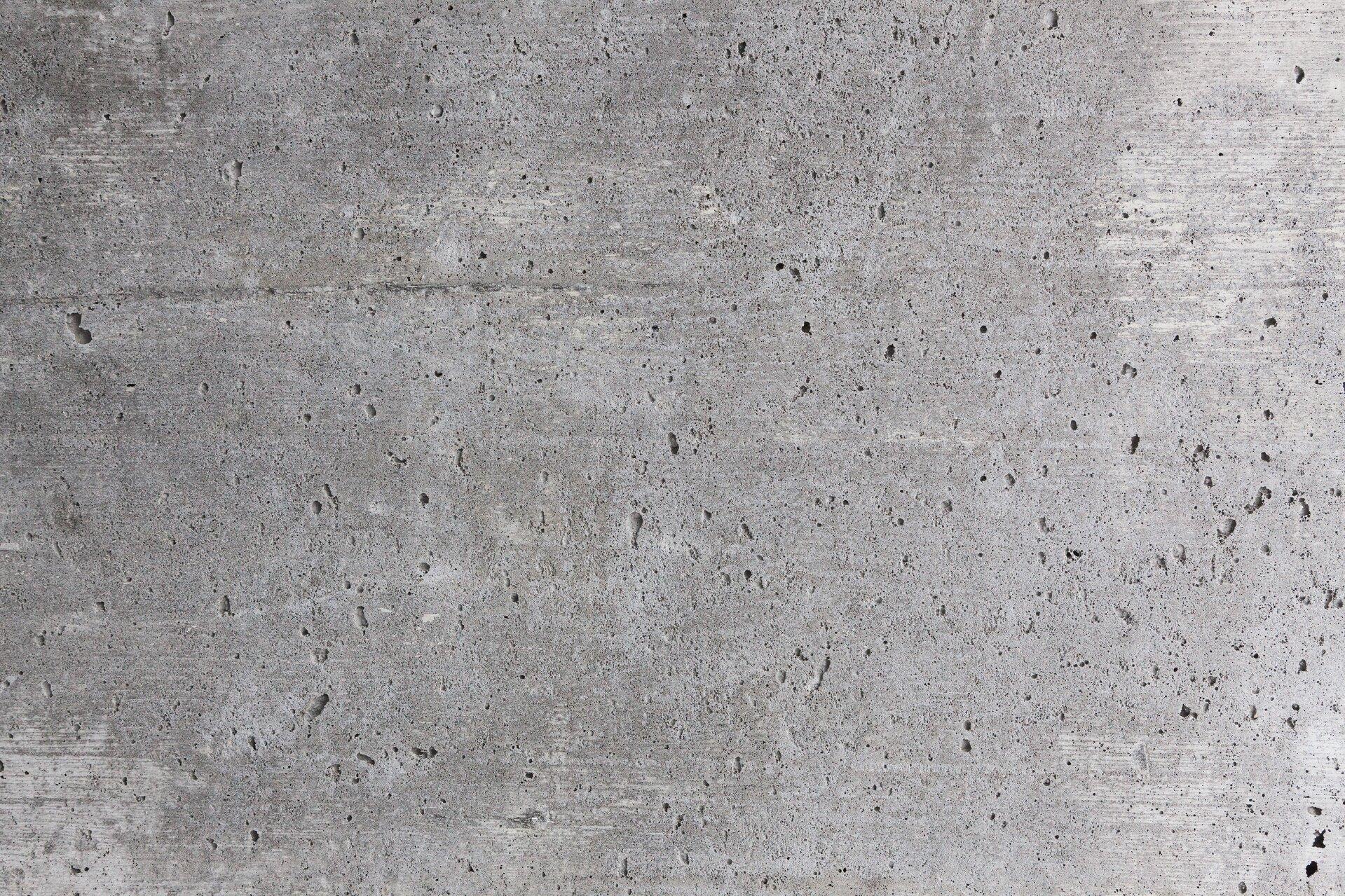 Zdjęcie przedstawia betonową, szarą ścianę zwidocznymi rowkami wnieco ciemniejszym kolorze.