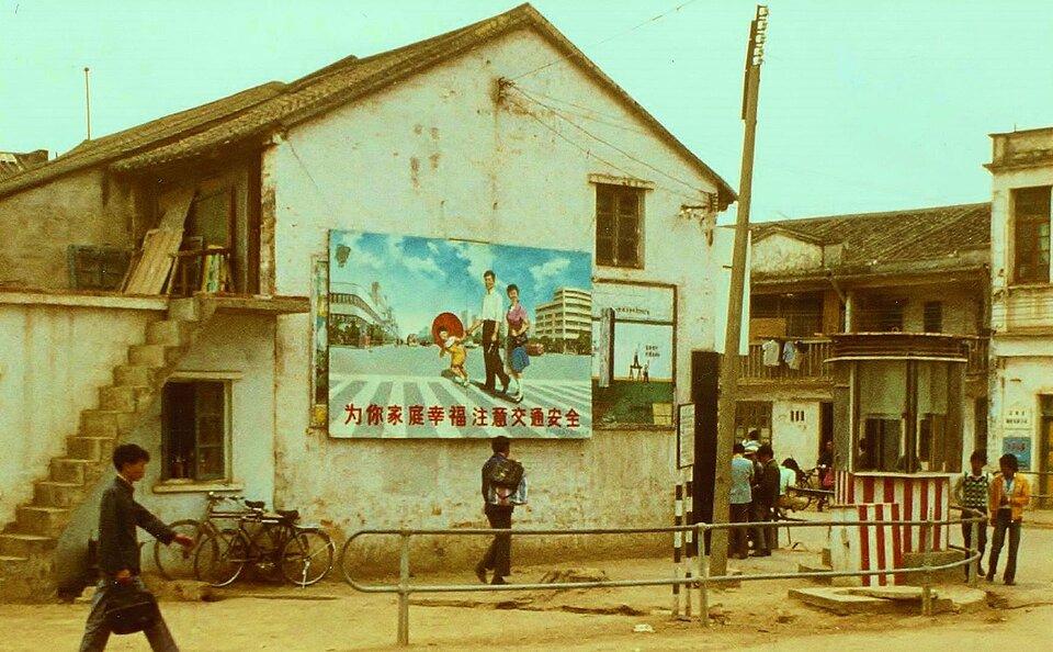 Na zdjęciu ulica, niska zabudowa, na ścianie domu tablica propagandowa. Uśmiechnięta rodzina zjednym dzieckiem.