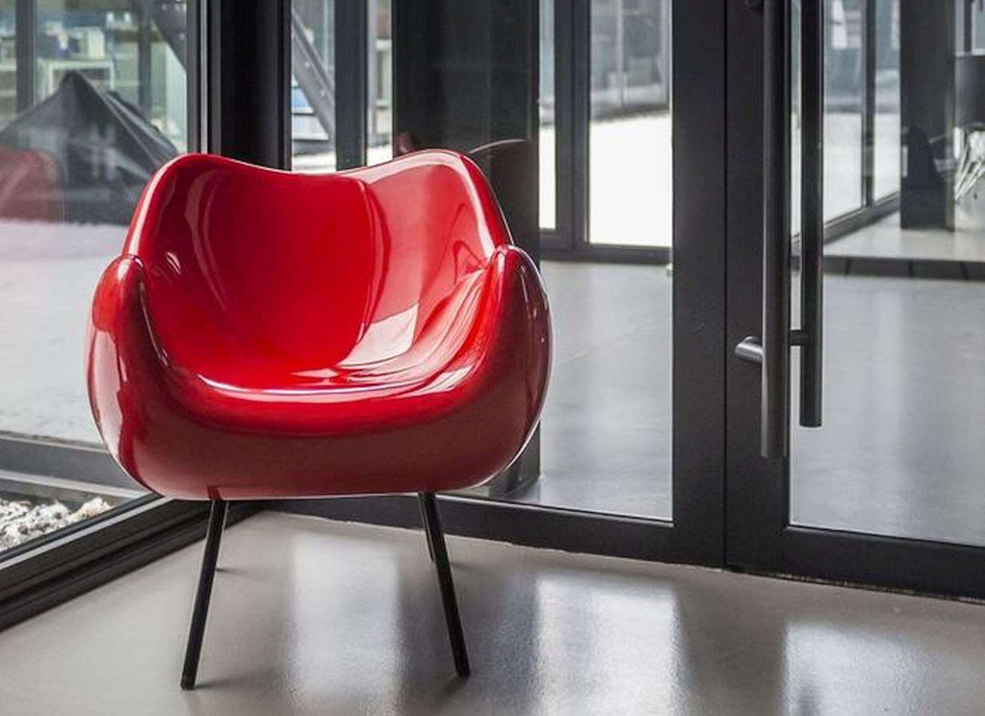 Ilustracja przedstawia projekt fotela autorstwa Romana Modzelewskiego. Jest to czerwony plastikowy fotel stojący na czterech cienkich, długich nogach. Fotel stoi wpomieszczeniu przed drzwiami.