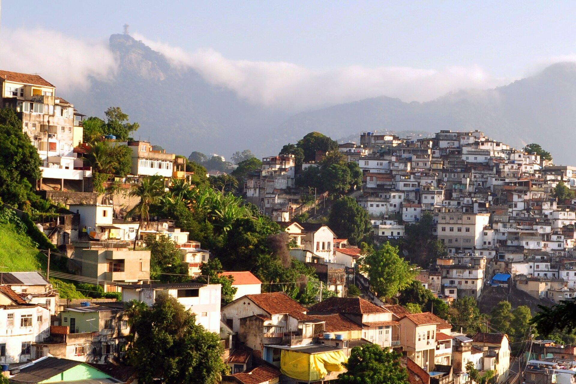 Na zdjęciu rozległa biedna dzielnica wBrazylii. Teren górzysty, dwa wzniesienia. Proste domki wzniesione kaskadowo na wzgórzu. Część ma dachy proste, część spadziste, kryte dachówką. Wtle wysokie góry.
