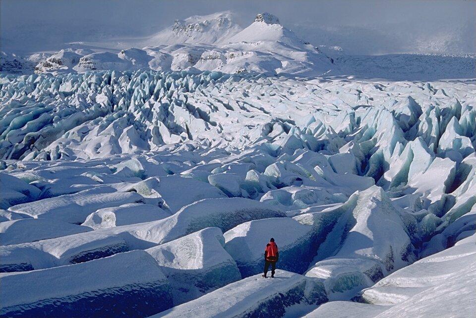 Na zdjęciu rozległy lodowiec, dużo szczelin ispękań, wtle wysokie ośnieżone góry, na pierwszym planie człowiek.