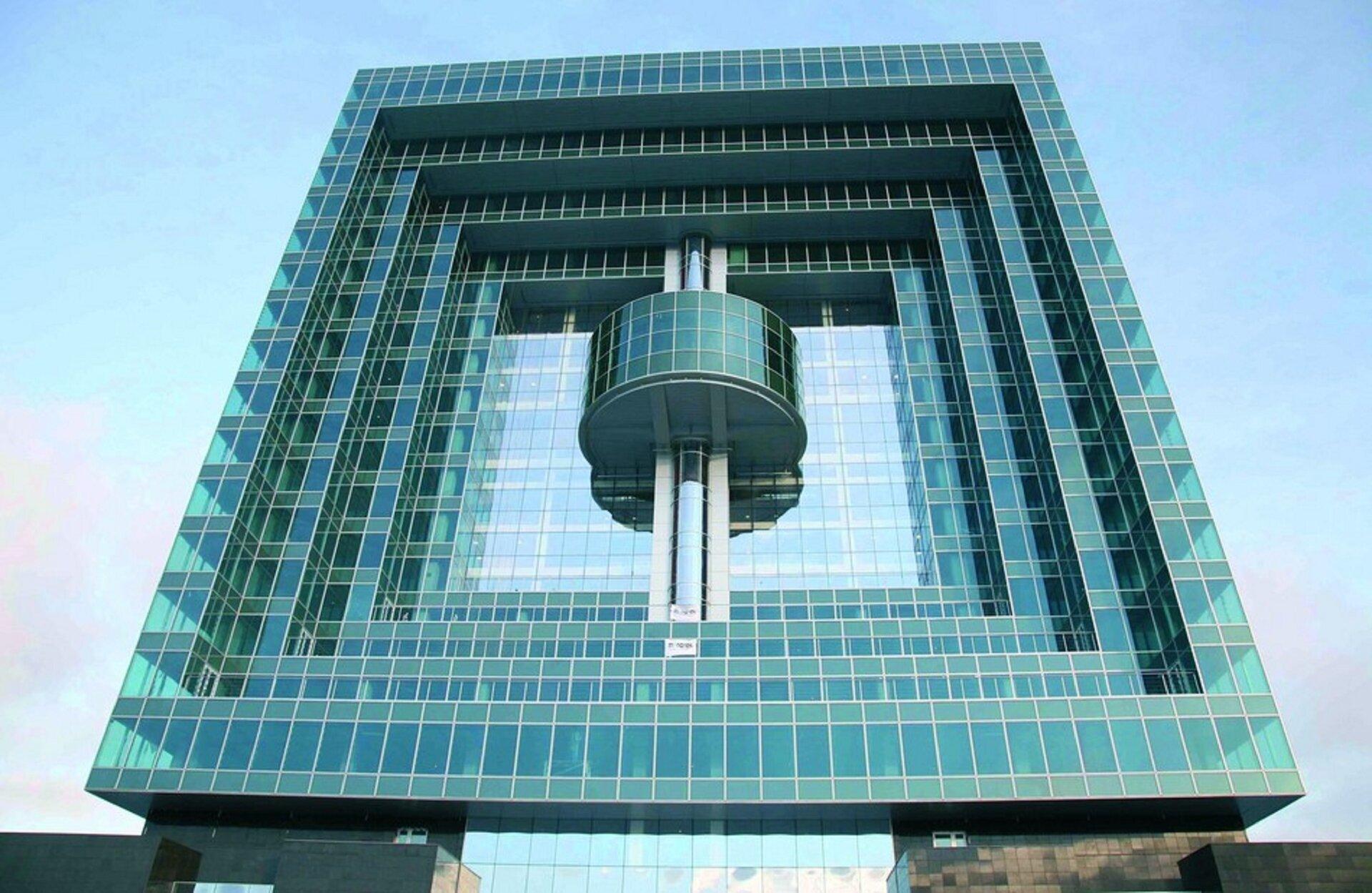Ilustracja przedstawia Avilon Plaza wMoskwie. Jest to budynek ze szklaną elewacją. Konstrukcja to cztery kwadraty wpisane jeden wdrugi. Wnajmniejszym znich są trzy filary, ana środku nich półokrągła część wystająca zbudynku również pokryta szkłem. Szklana elewacja ma kolor zielonkawo-niebieski. Wtle jasne błękitne niebo.