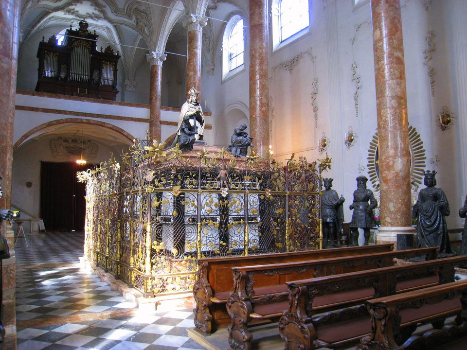 Wnętrze kościoła. Drewniane ławki stoją na podłodze wyłożone czarnymi ibiałymi kwadratami. Pod ścianami stoją marmurowe, różowe kolumny, amiędzy nimi rzeźby postaci wkoronach. Wcentralnej części stoi grobowiec otoczony zdobioną kratą wkolorze złotym, ana jego szczycie stoi rzeźba postaci wkoronie.