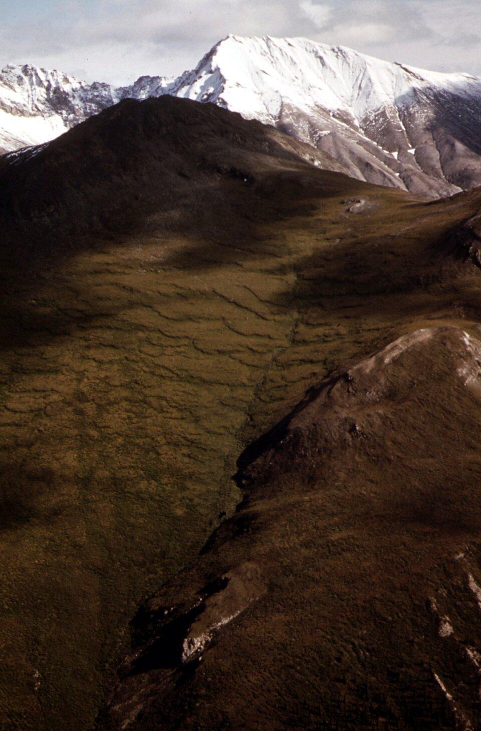Na zdjęciu teren górzysty. Na pierwszym planie zsuwające się brązowe fale gruntu. Wtle wysokie ośnieżone szczyty.