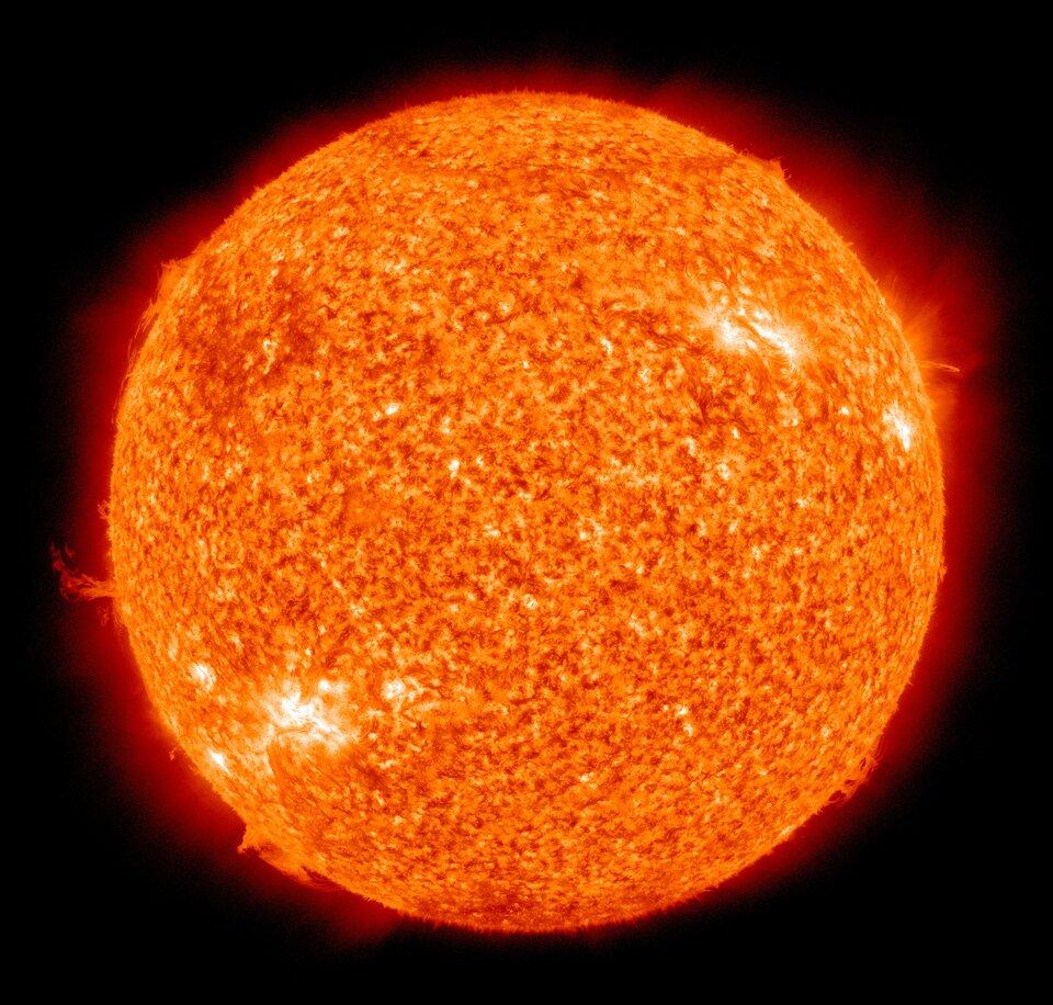 Zdjęcie przedstawia Słońce sfotografowane wpodczerwieni. Tło czarne. Słońce wygląda jak pomarańczowa kula ognia.