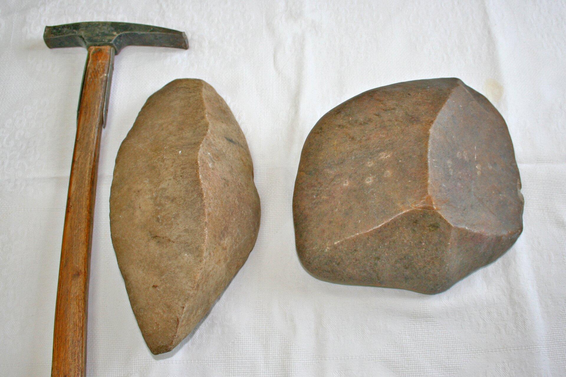 Na zdjęciu dwa graniaki. To fragmenty skał zpowierzchnią wygładzoną przez wiatr iwyraźnymi krawędziami. Obok dla porównania wielkości leży młotek geologiczny. Graniaki są nieco mniejsze od młotka.