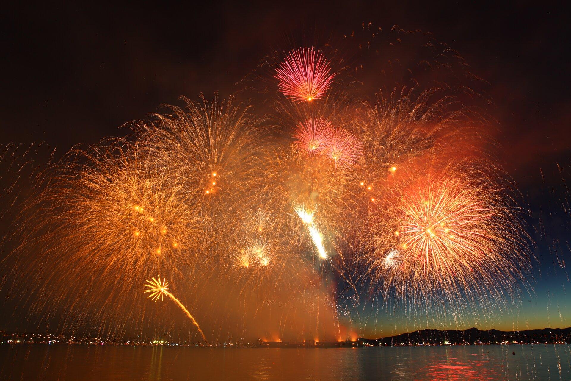 Zdjęcie przedstawia nocne niebo nad miastem leżącym nad jeziorem lub brzegiem morza ibardzo efektowny pokaz fajerwerków.