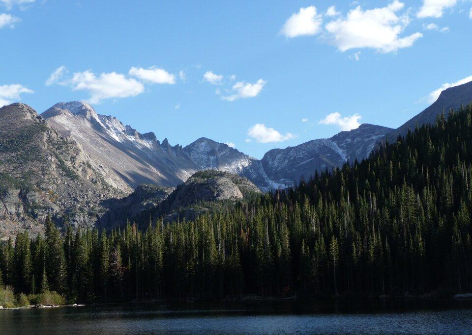 Na zdjęciu wysokie, odsłonięte, skaliste szczyty, na pierwszym planie las iglasty, zbiornik wodny.