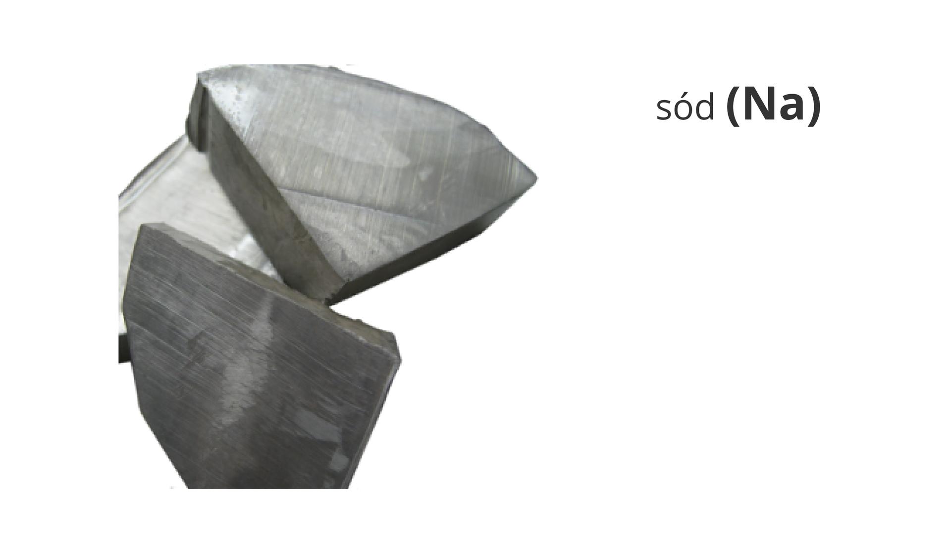 Zdjęcie przedstawia bryłki metalicznego sodu. Obok widnieje napis sód ijego symbol Na.