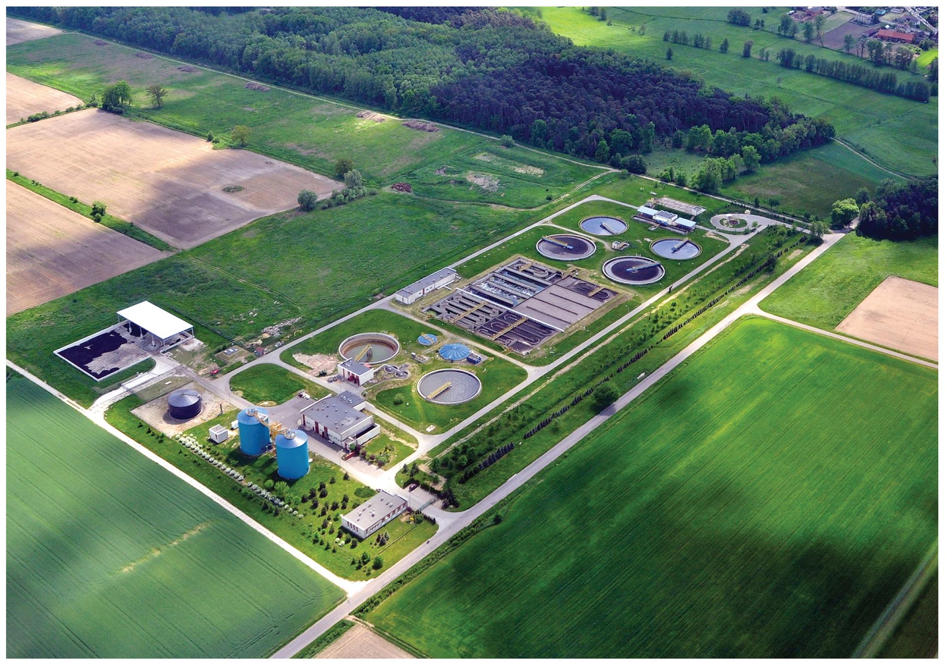 Fotografia przedstawia budowlę techniczną, widzianą zgóry. Znajdują się tam cztery okrągłe zbiorniki, dwa silosy iwiele budynków. Jest to biologiczna oczyszczalnia ścieków. Tu bakterie rozkładają organiczne składniki ścieków