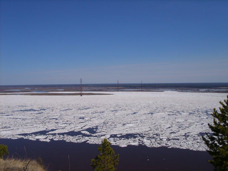 Na zdjęciu szeroka rzeka pokryta lodem.