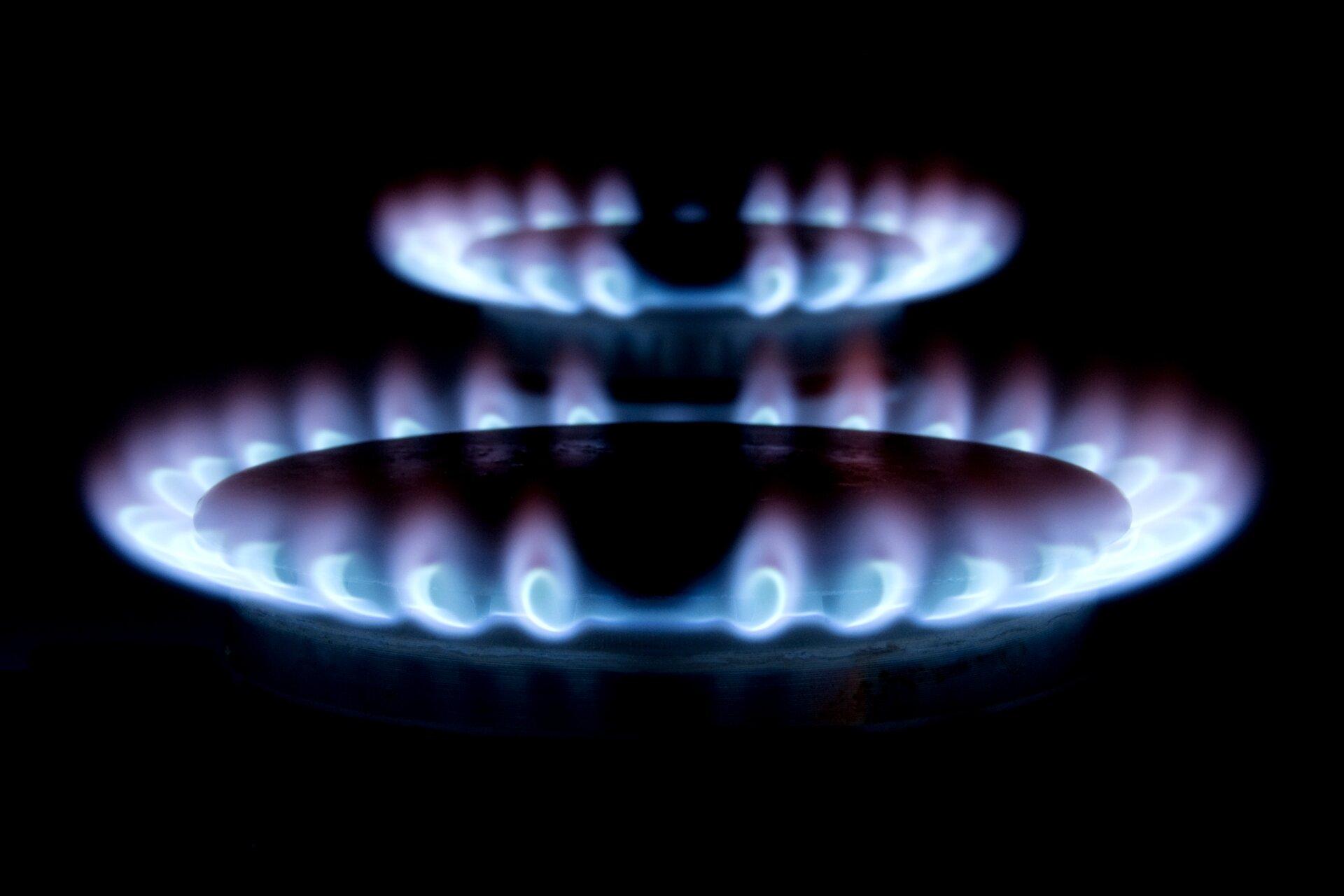 Zdjęcie przedstawia dwa czynne palniki kuchenki gazowej płonące wciemnościach.